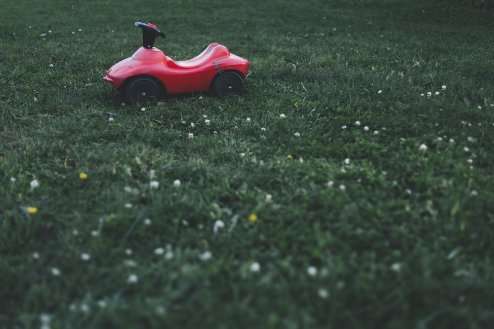 red ride-on toy car on grass field