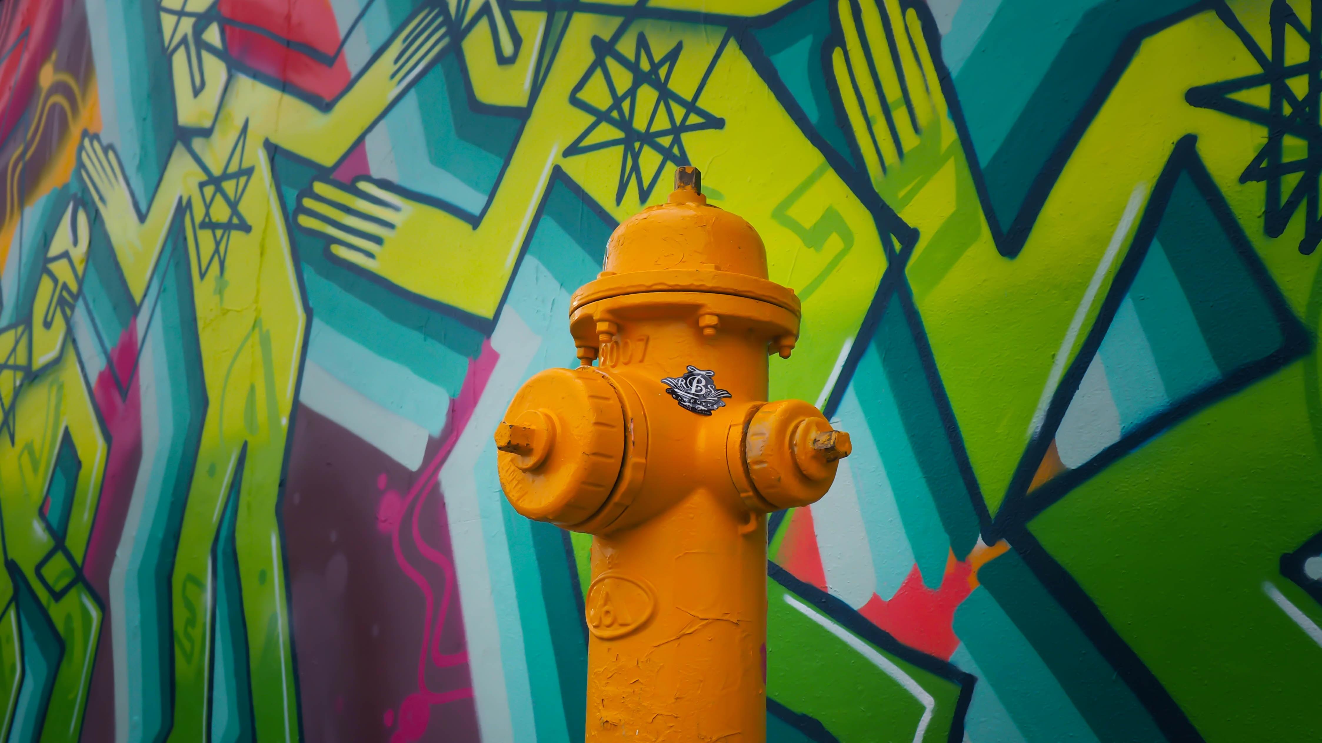orange fire hydrant near mural wall