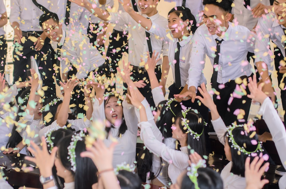 people in white shirts throwing confetti