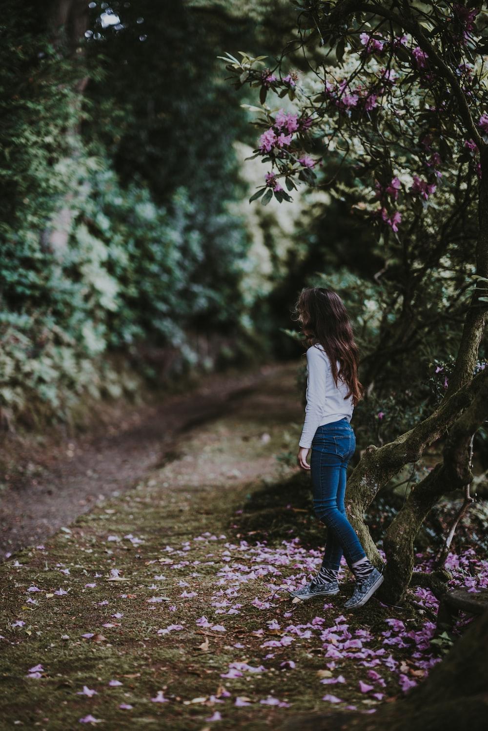 woman walking on pathway near trees