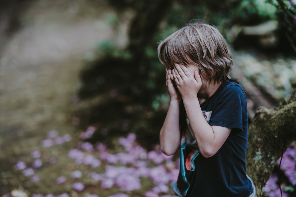 boy covering his face while standing