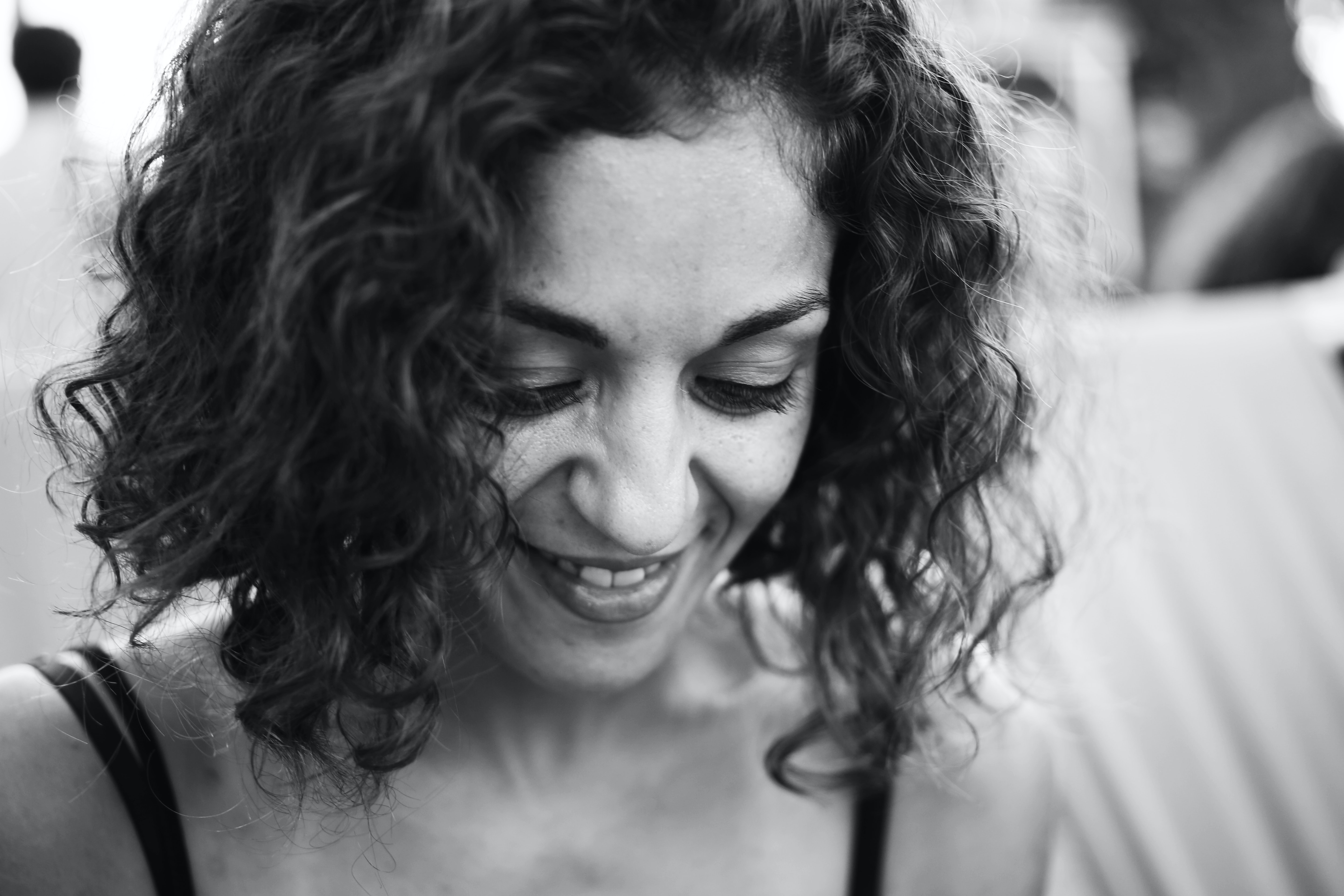 grayscale photo of smiling woman wearing spaghetti strap top