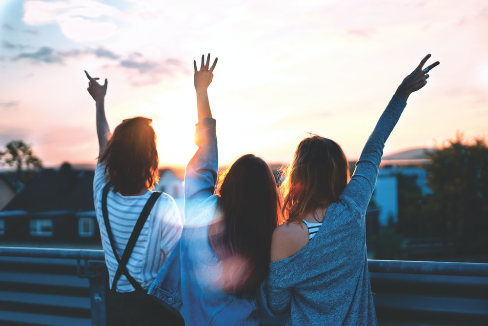 photo of three women lifting there hands \