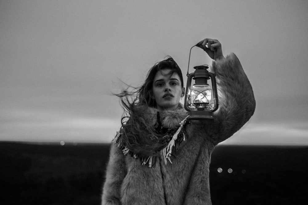 grayscale photography of woman holding lantern