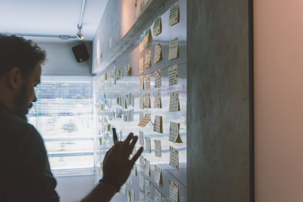 male putting sticky notes on wall