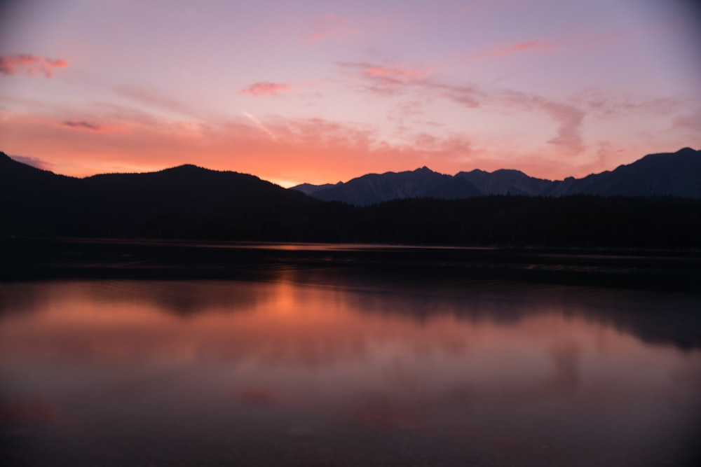 silhouette of mountain reflected on body of water