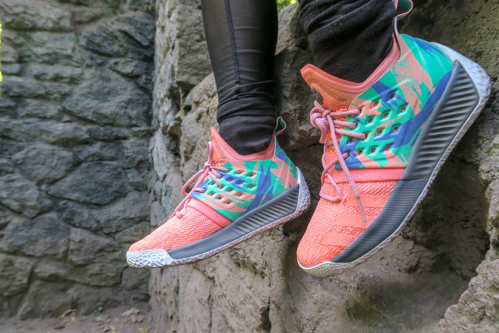 person wearing teal-and-orange adidas sneakers