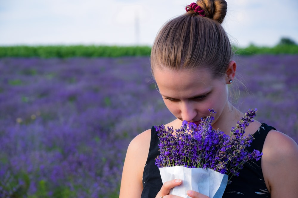 woman smelling bouquet of purple lavender