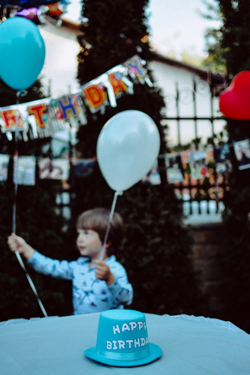 boy holding blue and white balloons at the party