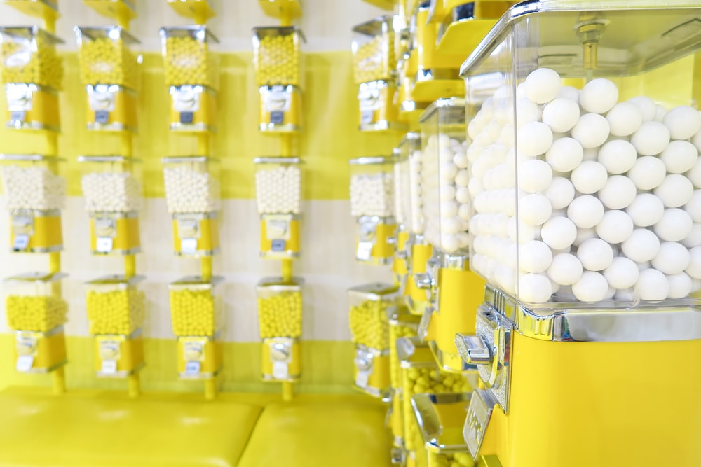 yellow candy dispenser filled with white candies