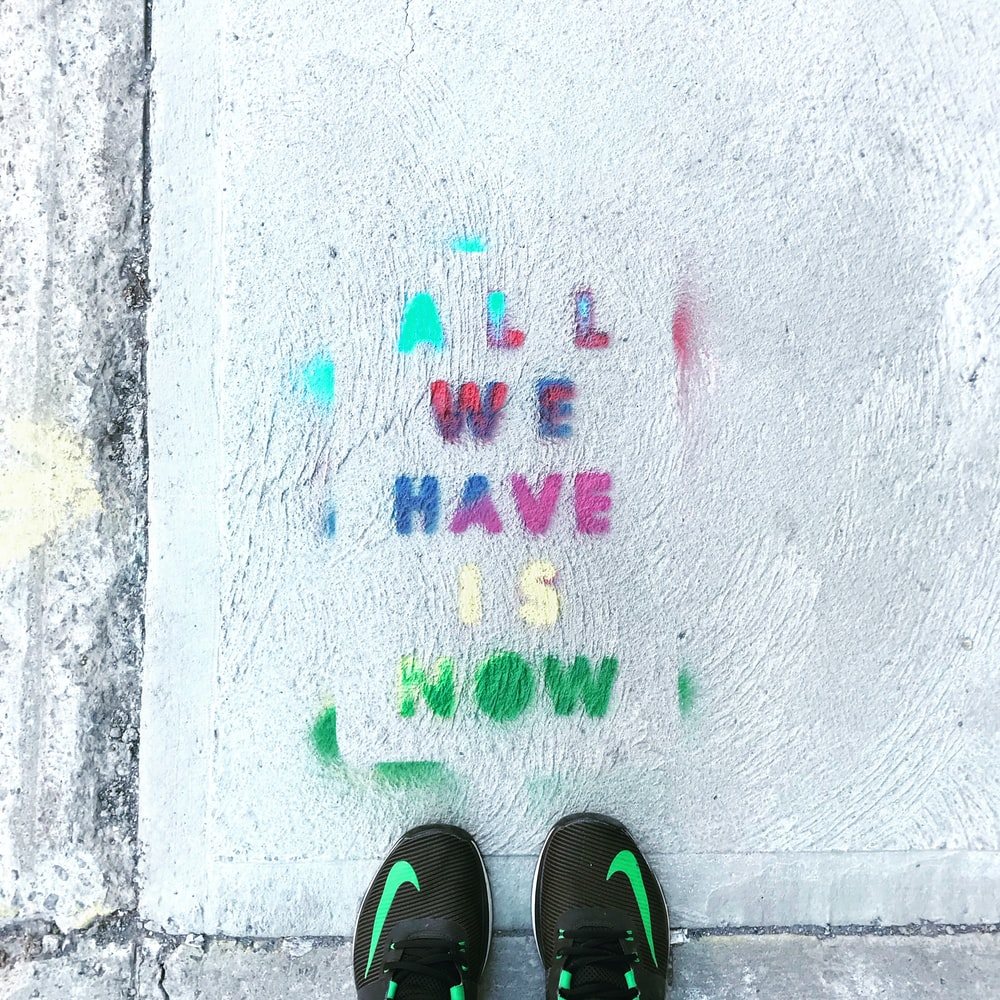 person standing on pavement with all we have is now written on it