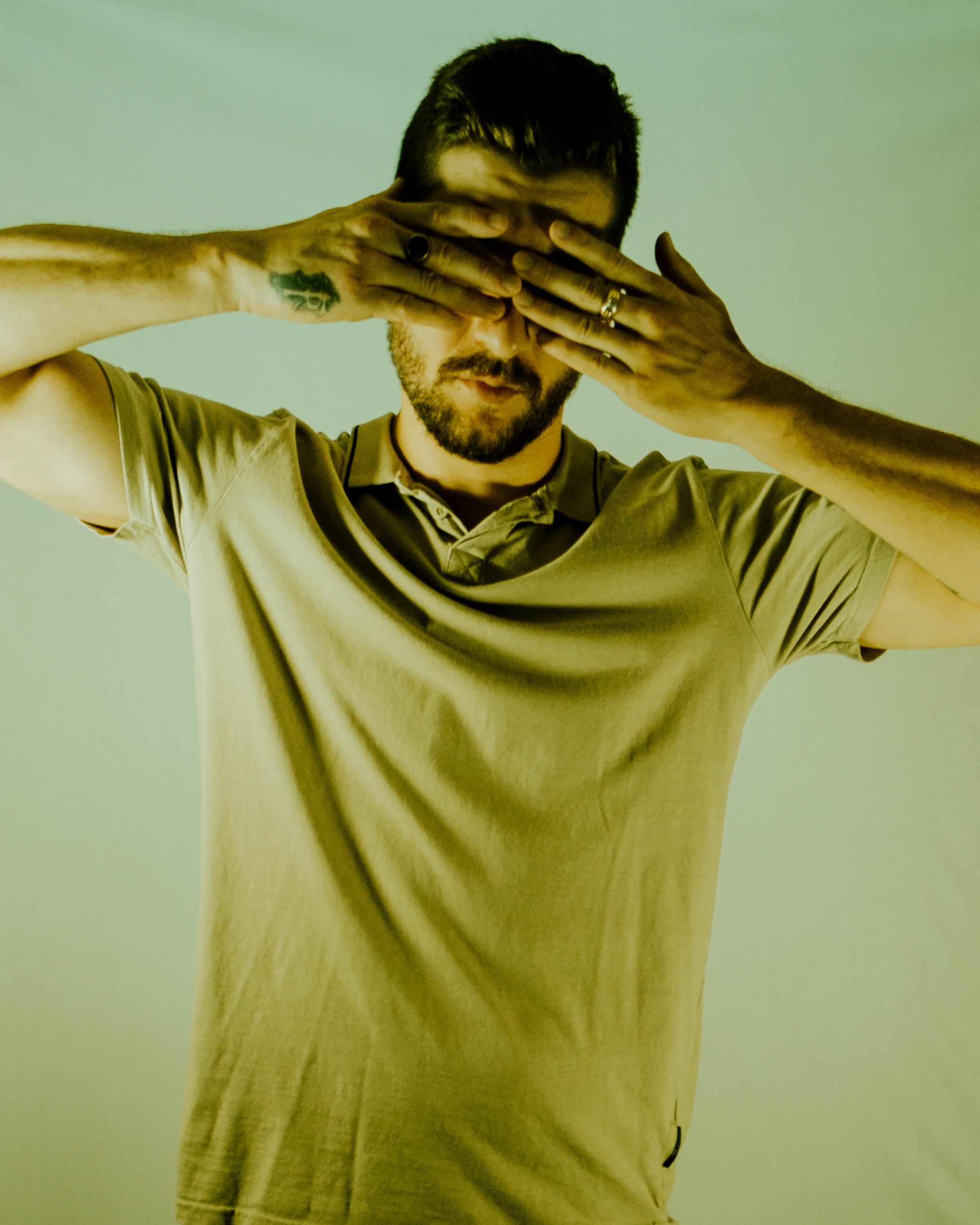 man covering his eyes using both hands