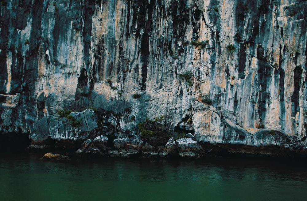 body of water beside gray cave