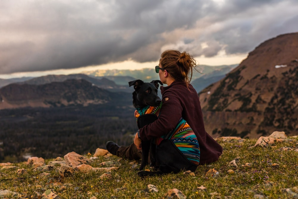 woman sitting beside black dog on mountain
