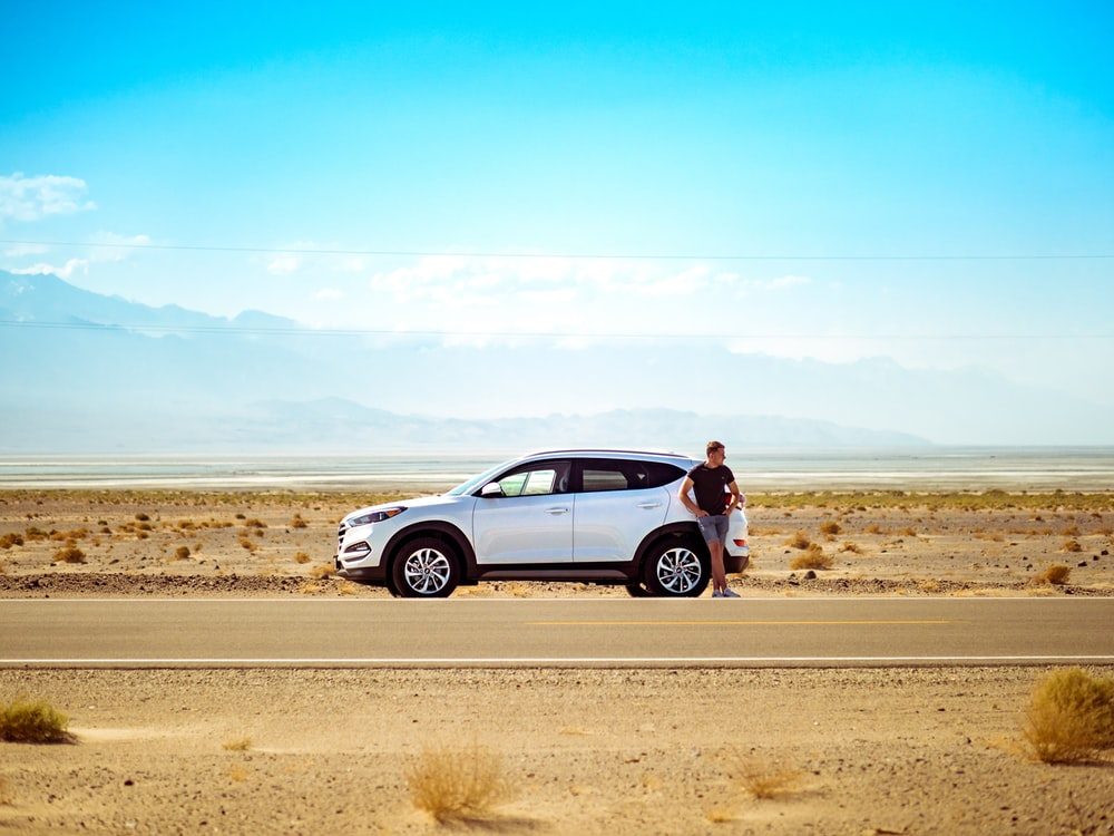 man standing beside white SUV near concrete road under blue sky at daytime