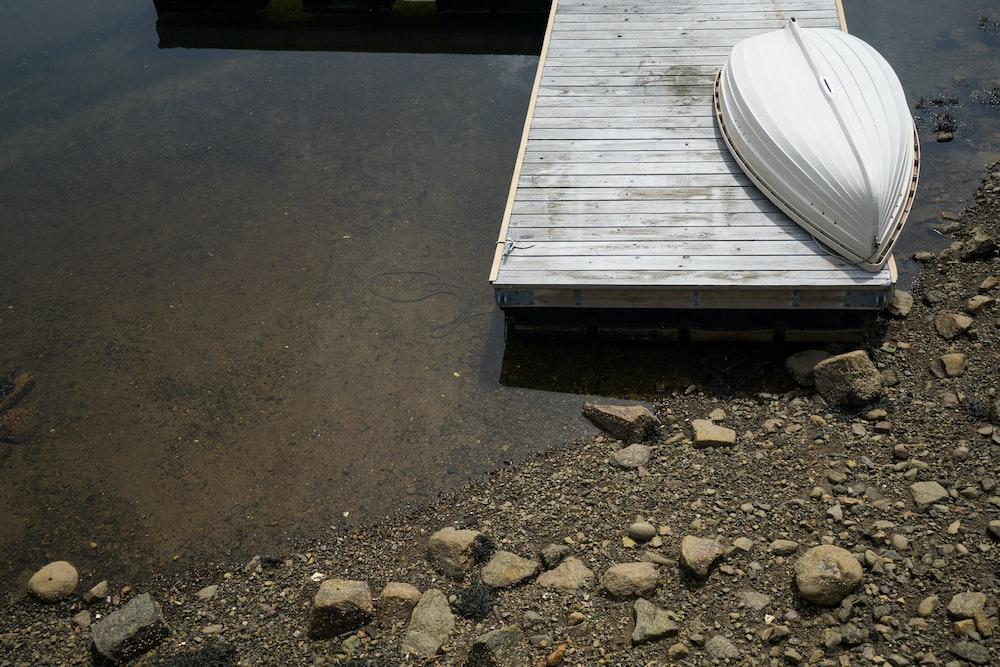 white boat on gray dock