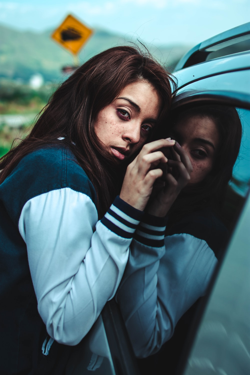 woman leaning in car mirror