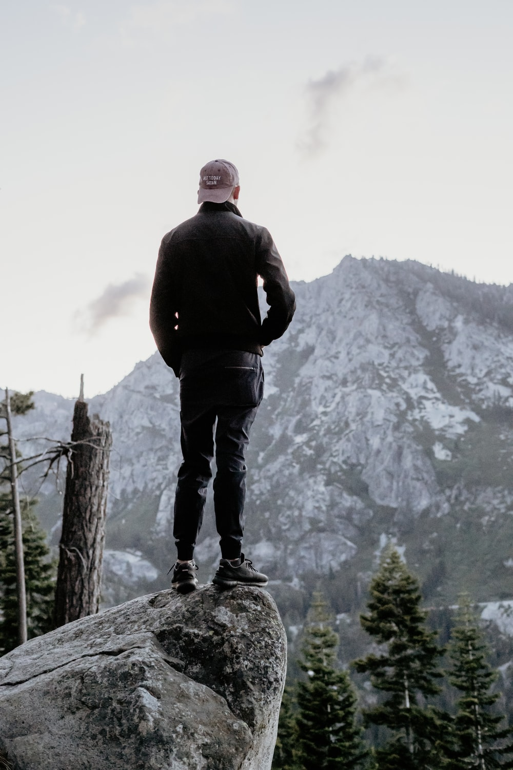 man standing on gray rock looking at mountain peak