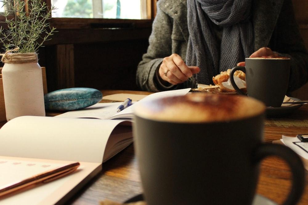black coffee mug near person eating
