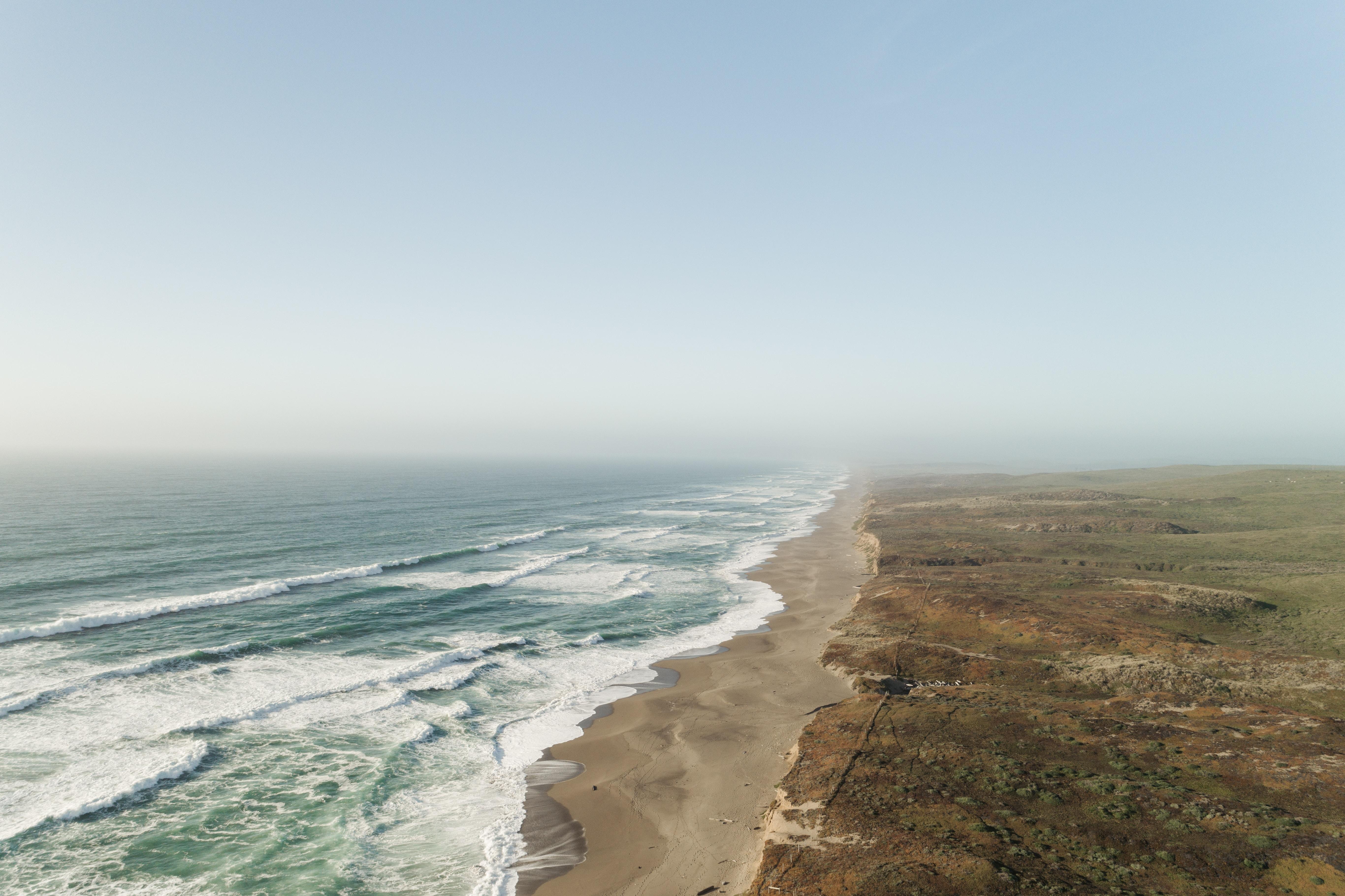 ocean near desert under white clouds during daytime