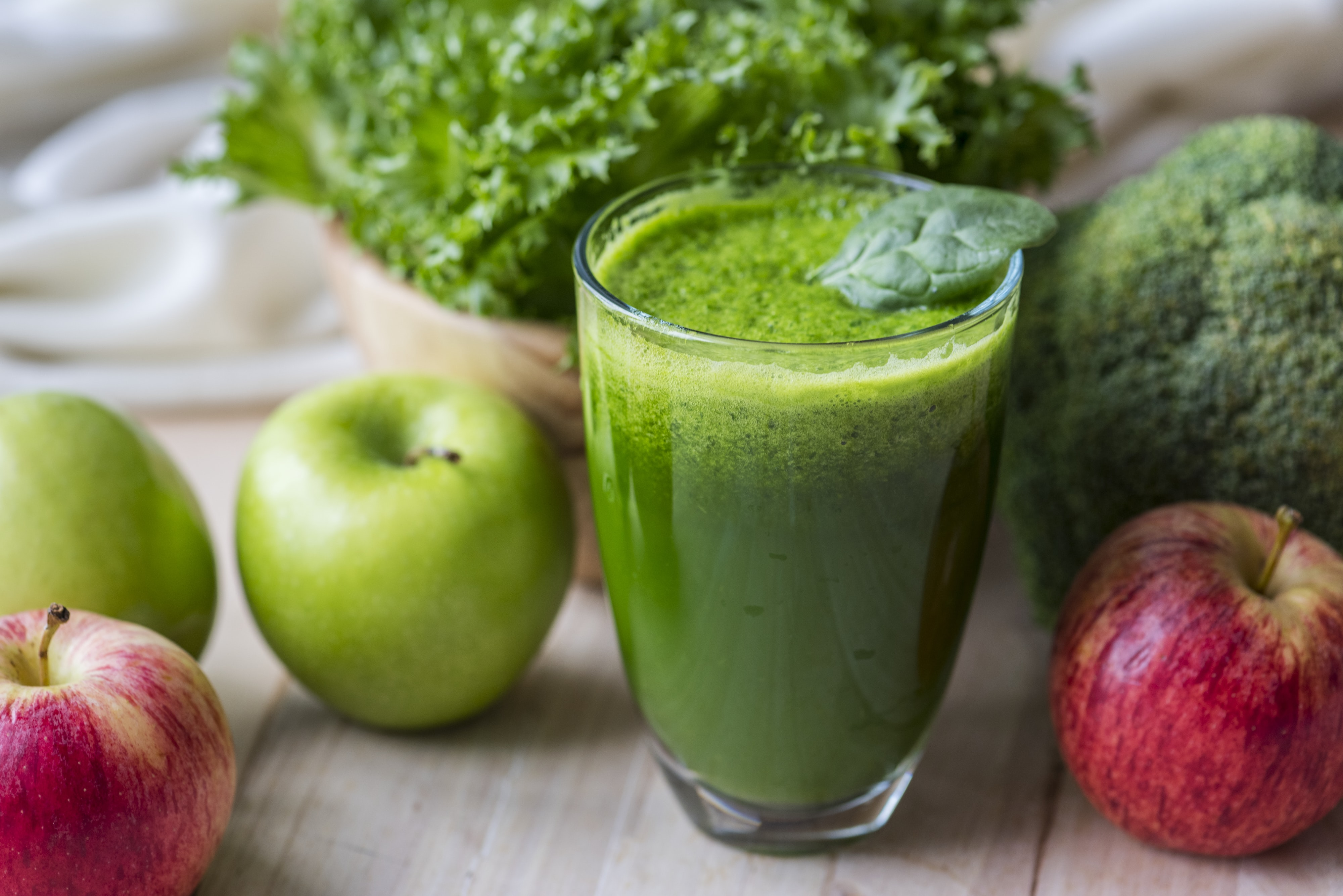 green apple juice in glass cup beside red and green apples