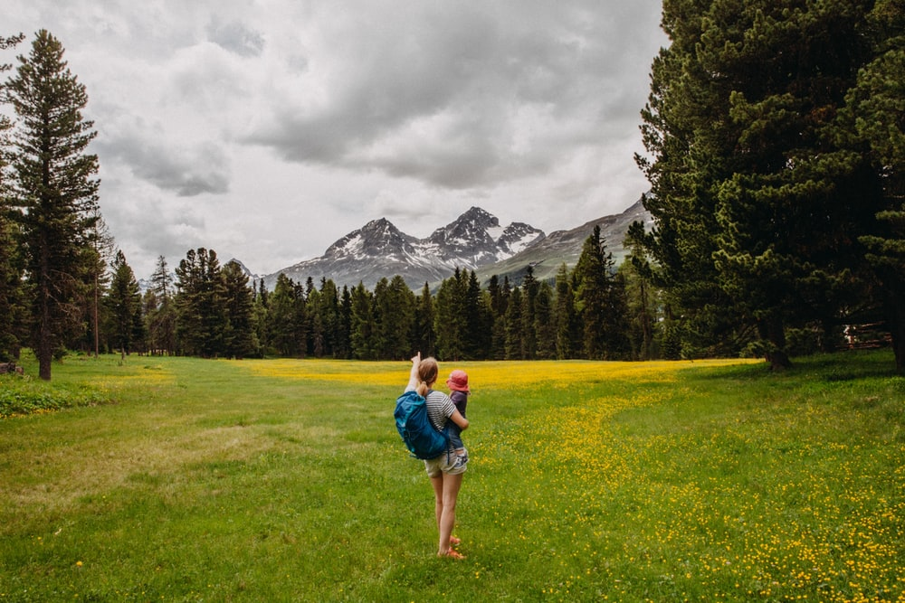 woman carrying toddler white pointing at snow-capped mountain under gloomy sky