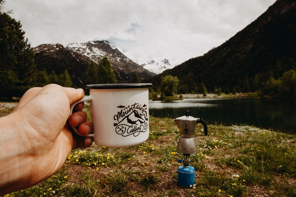 person holding white cup outdoors