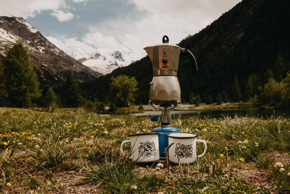 gray stainless steel mokapot on burner between two white mugs on green grass