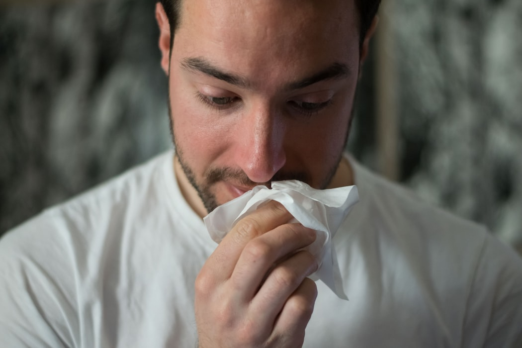 A man holding a tissue to his nose
