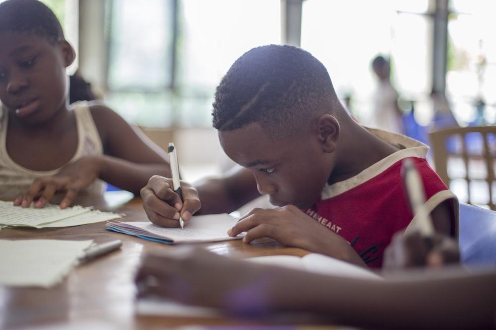 boy writing on printer paper near girl