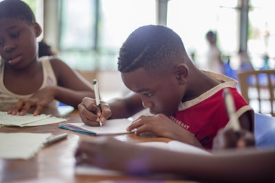boy writing on printer paper near girl equatorial guinea teams background