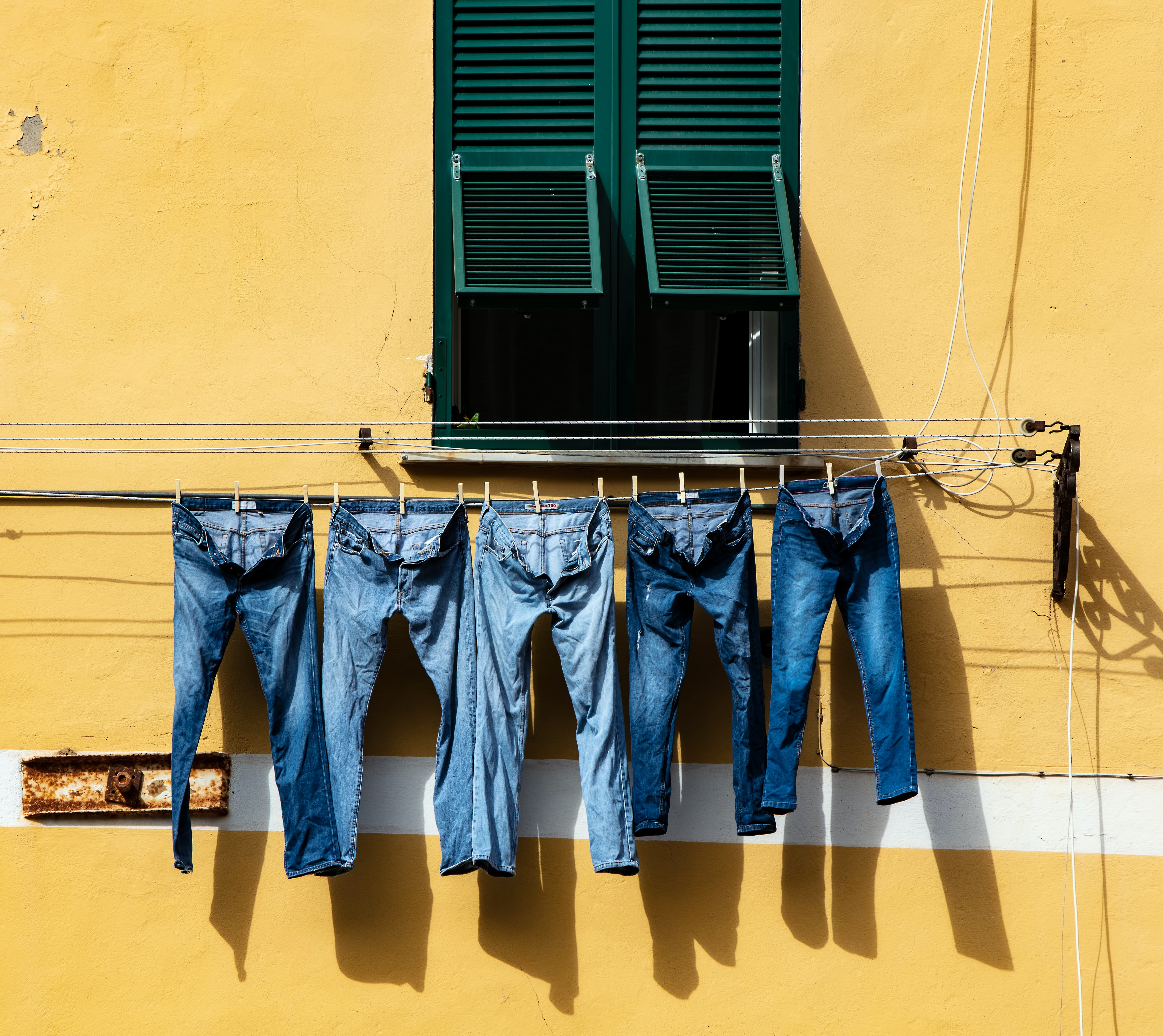 five blue denim jeans hanged on grey cable near window