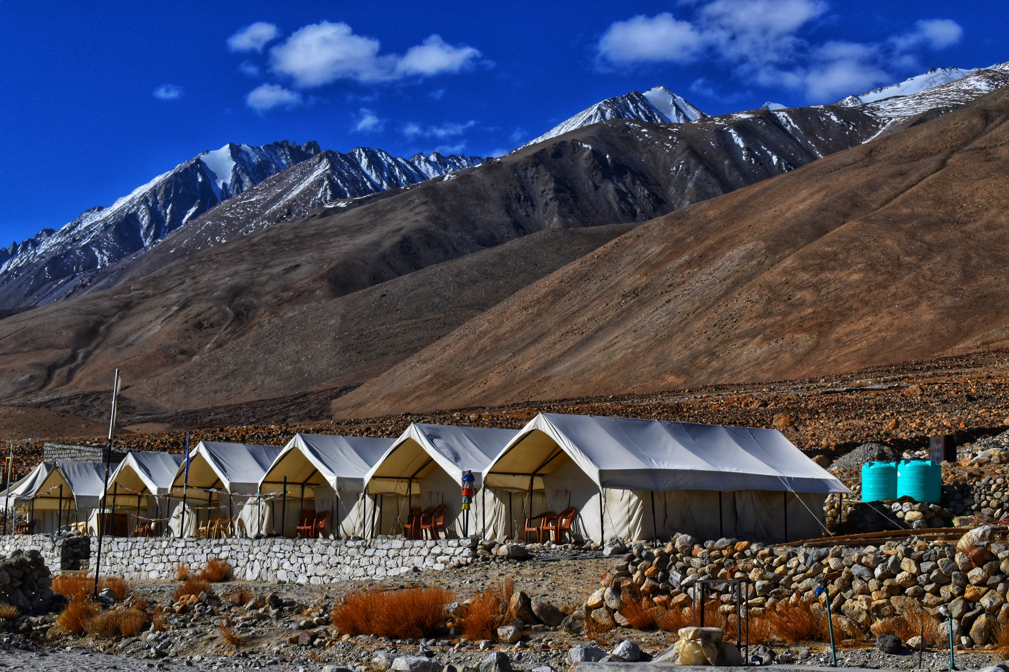 Tents in the backdrop of mountain ranges..