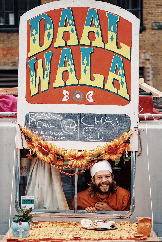 man inside Daal Wala store signage
