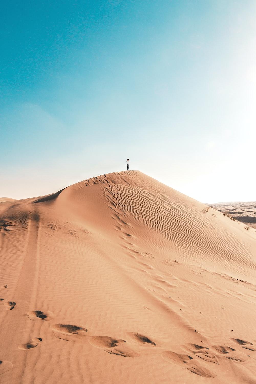 man standing on sand dune