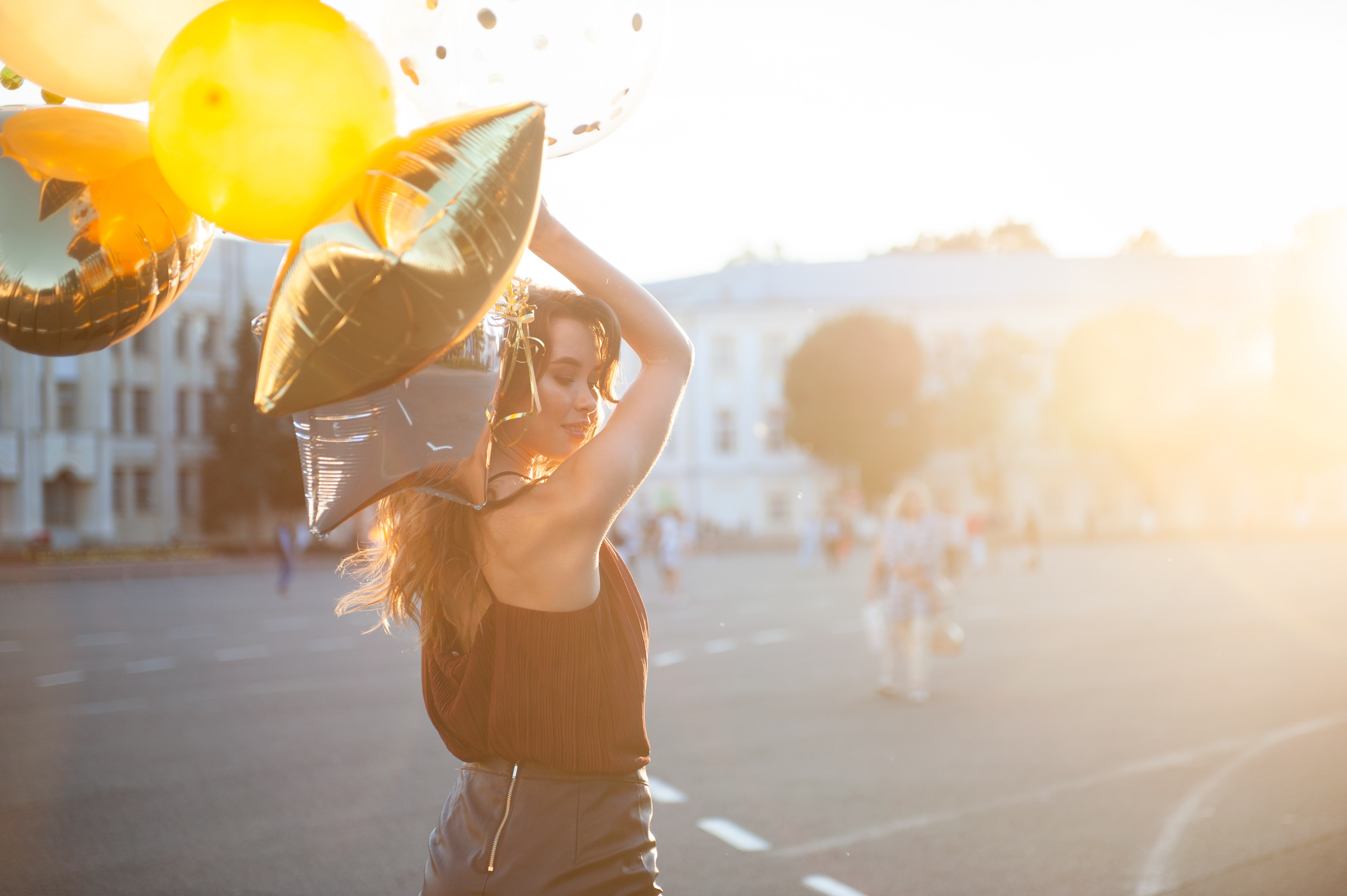 woman holding gold and silver foil balloons