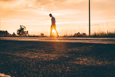golden hour photography of man walking on asphalt road