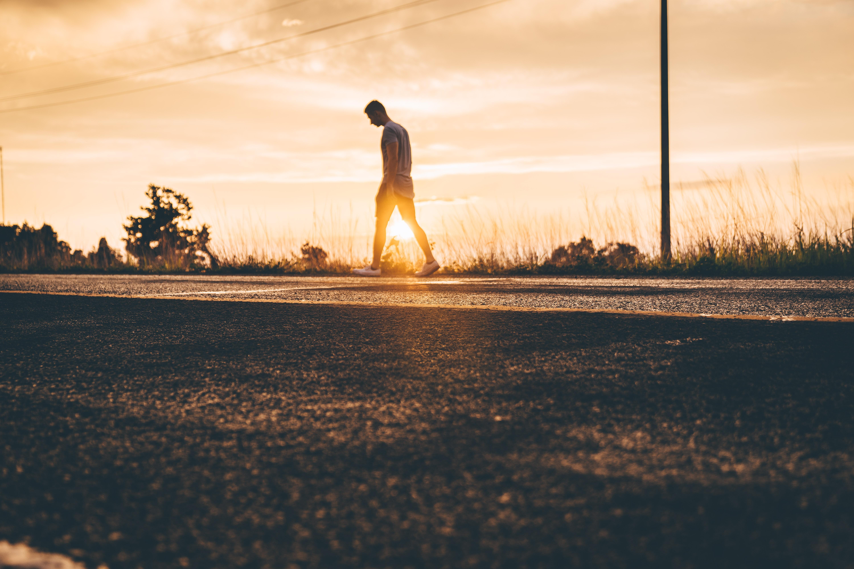 golden hour photography of man walking on asphalt road