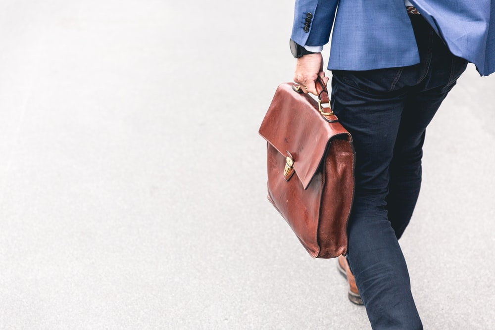 person walking holding brown leather bag