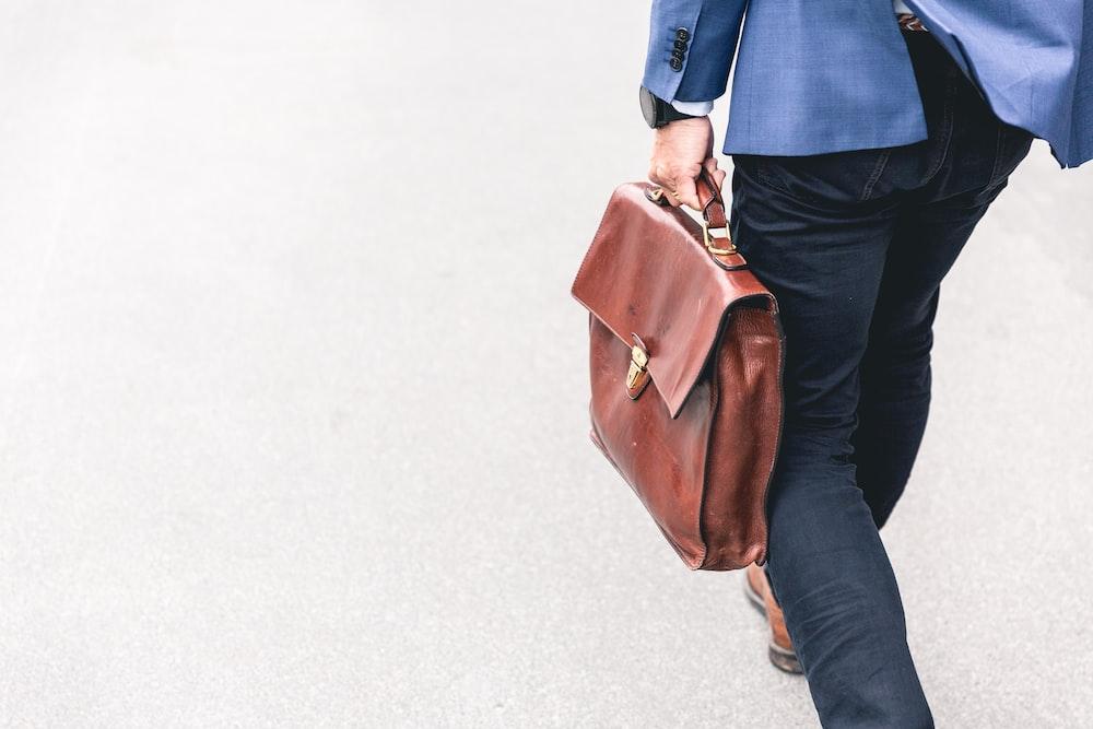 茶色の革のバッグを持って歩く人