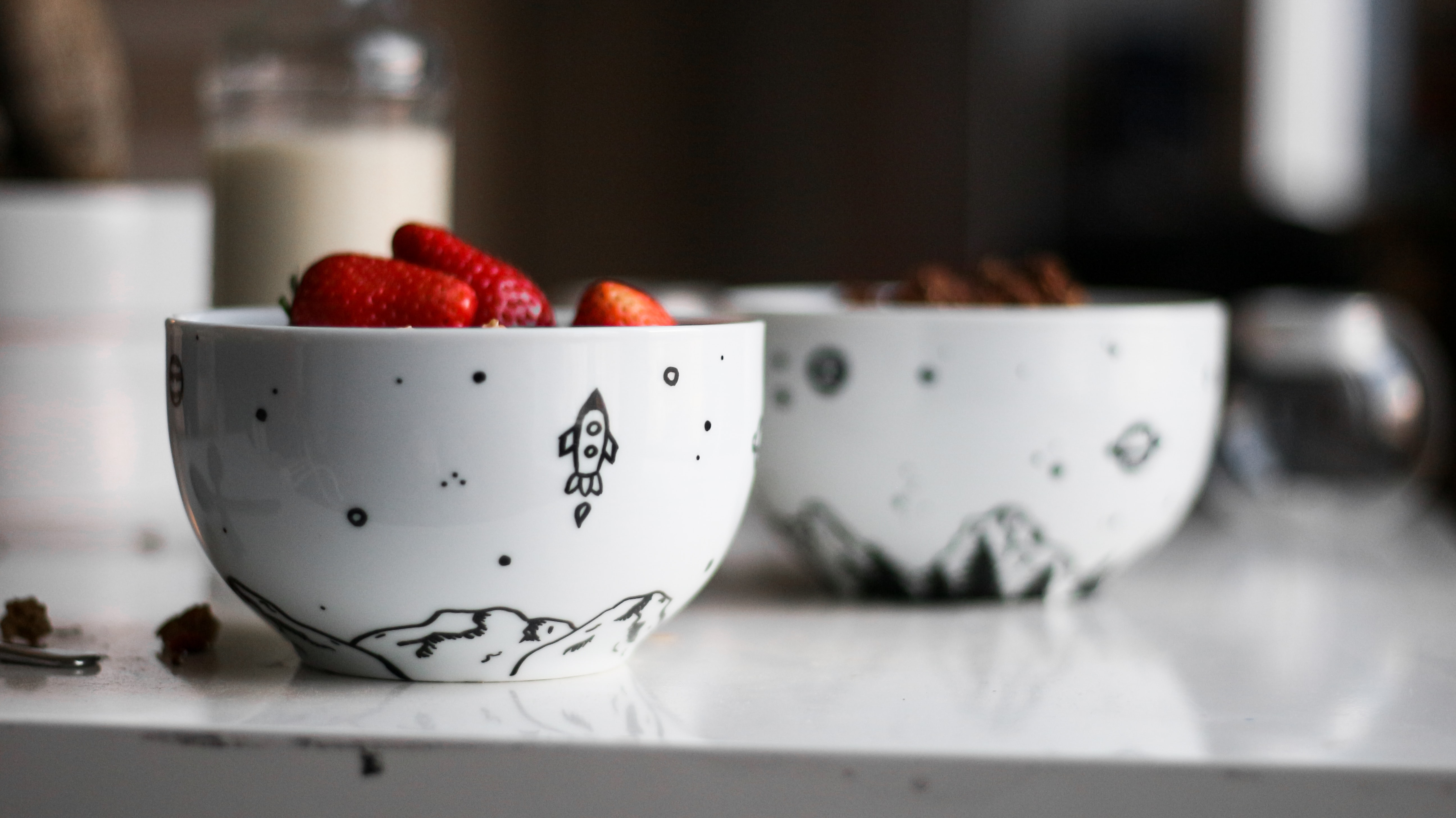 two white-and-black ceramic bowls on wooden table