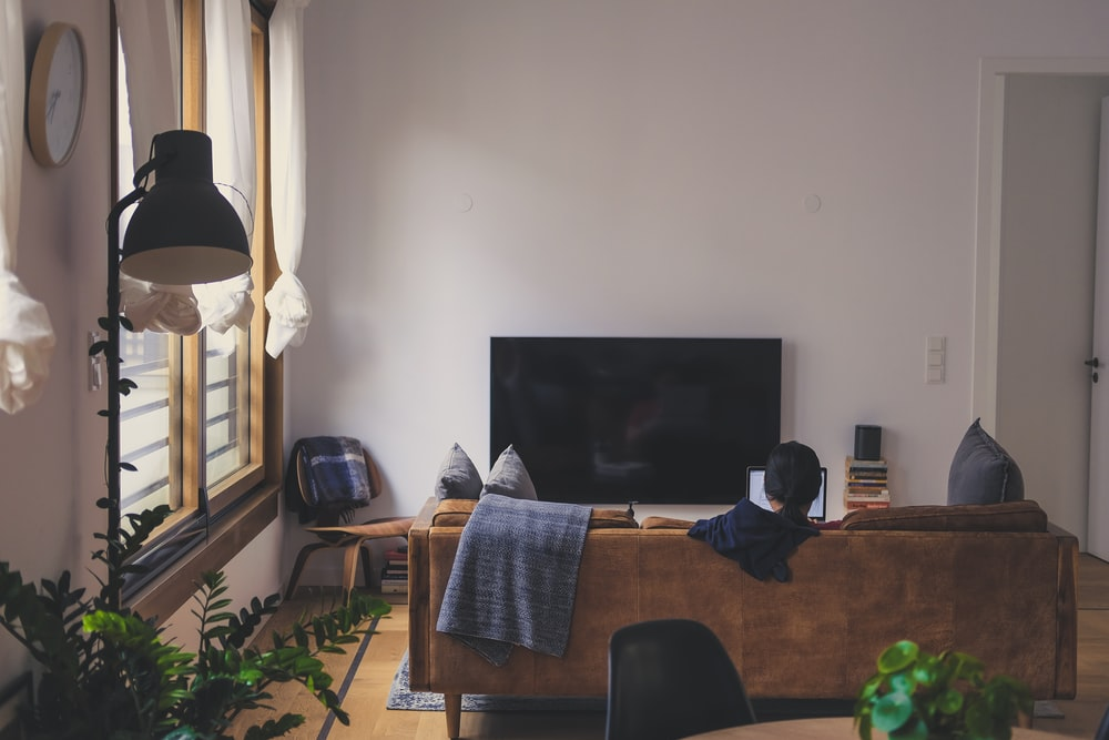 woman sitting on couch in front of LED TV