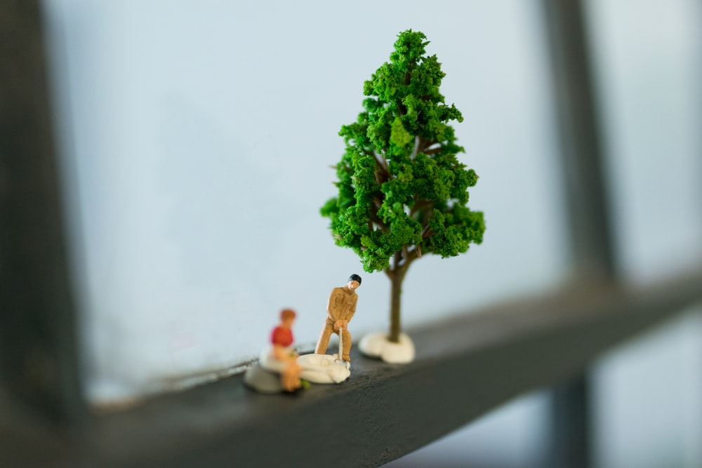 green tree and two men figurines
