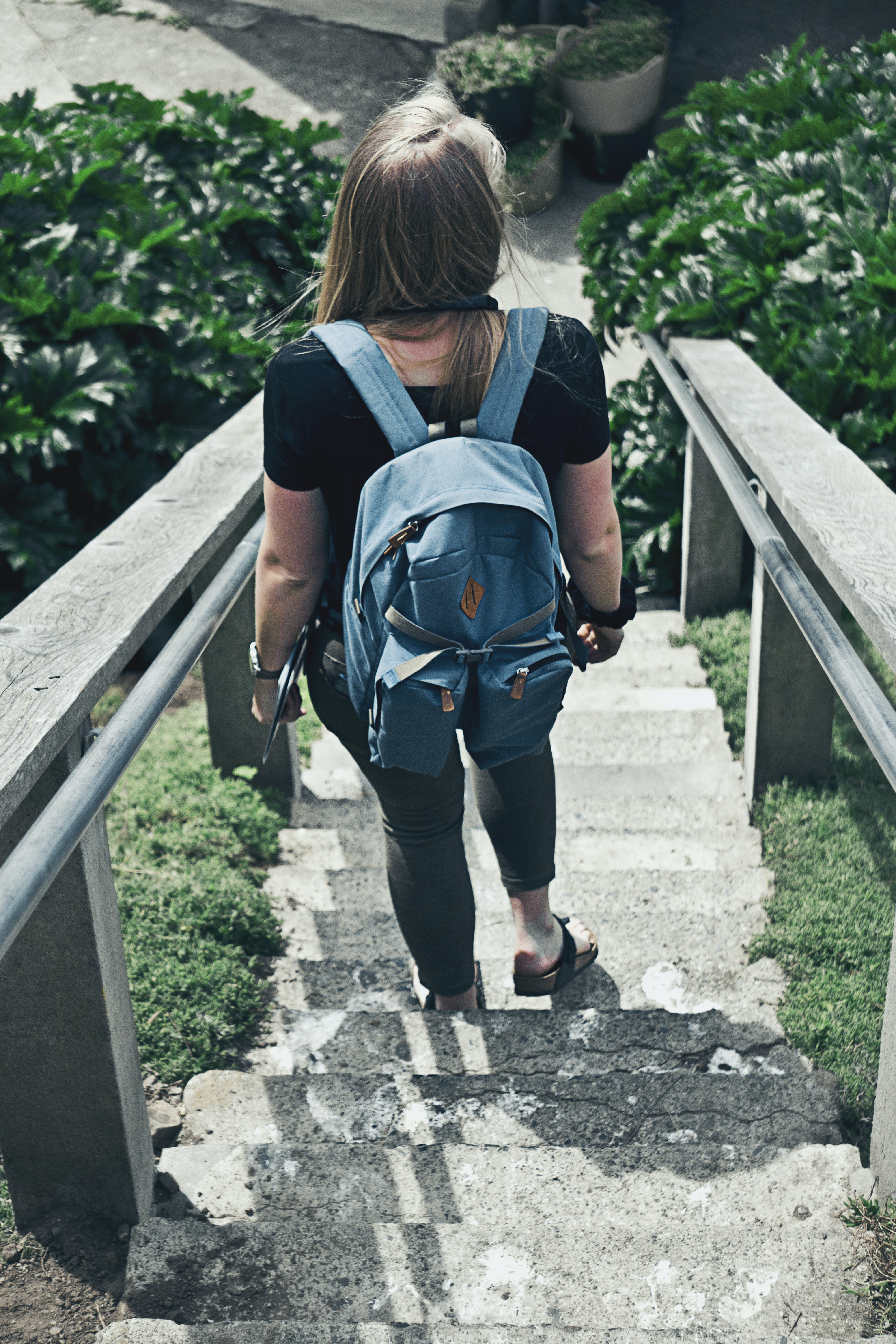 woman with backpack walking down on staircase