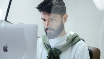 man facing MacBook Pro