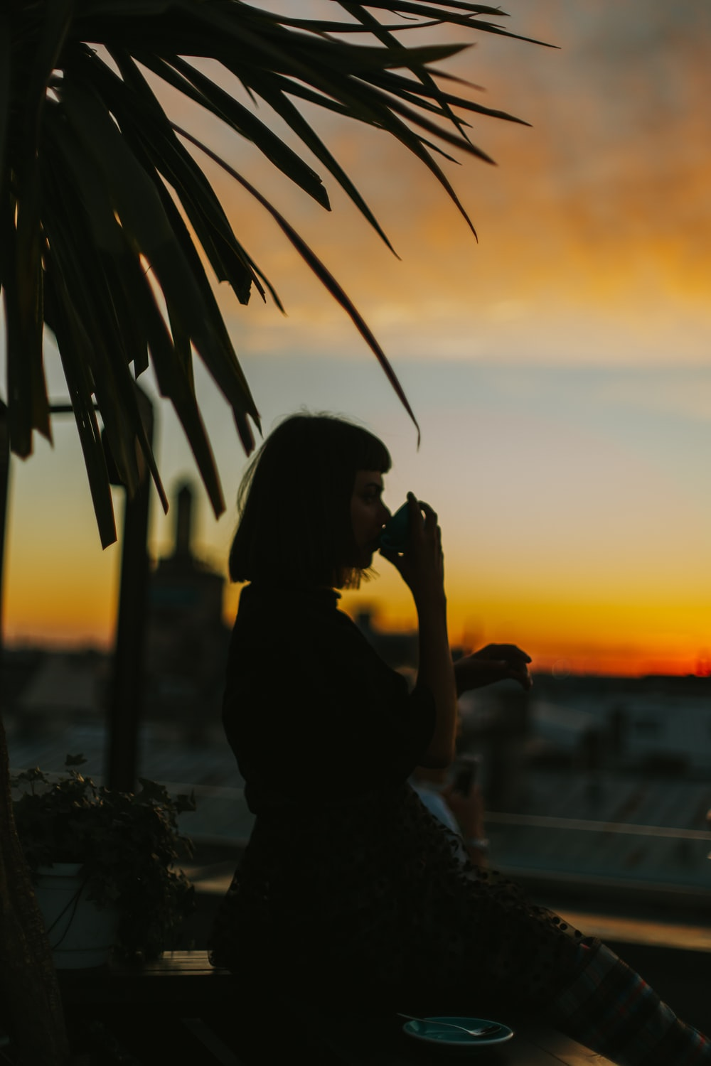 silhouette woman drinking from teacup during golden hour