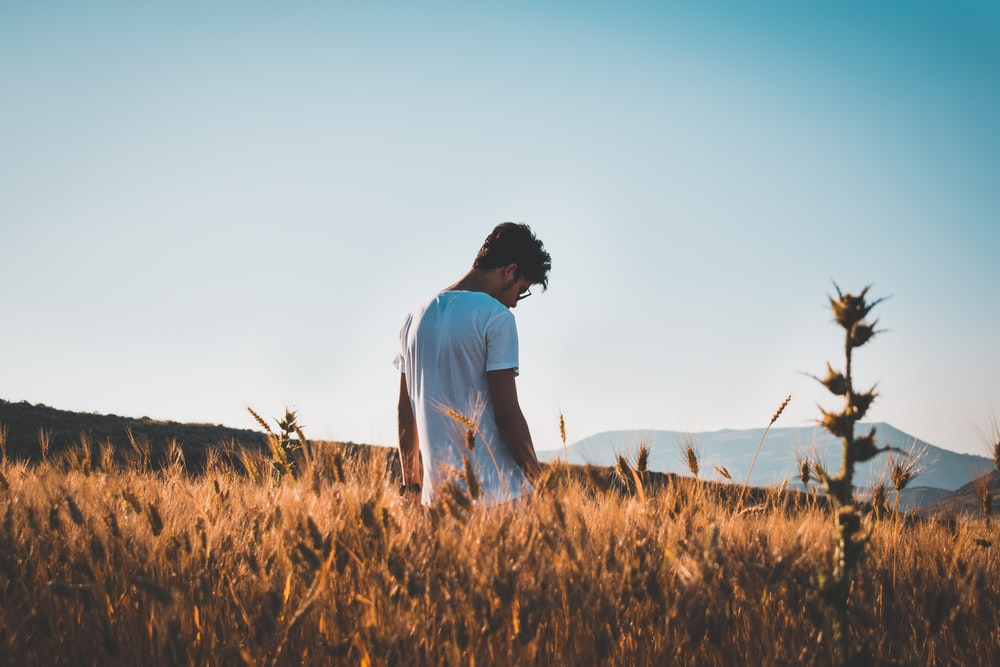 man in white top standing on brown grass