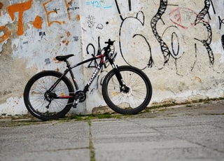 black hardtail bicycle leaning on white concrete wall
