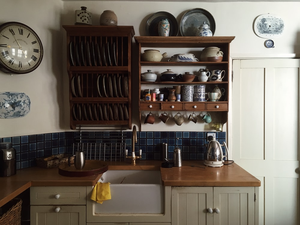 white kitchen cupboards and rack with dinnerware arranged on it