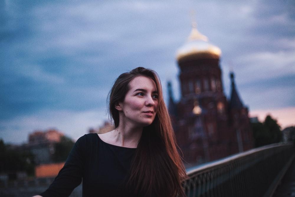 woman taking photo near building